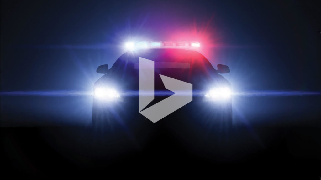 Police car with red and blue lights and head lights on in the darkness with the Bing logo 'B' on the front of the police car.
