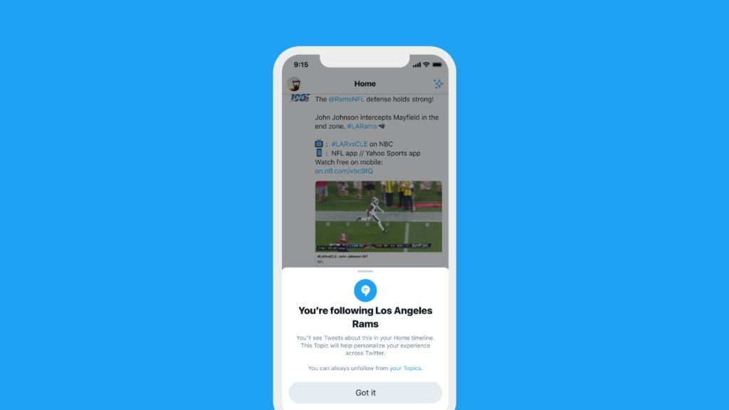 Image of a phone showing the Twitter interface darkened in the back with an announcement at the bottom saying ' You're following Los Angeles Rams' - You'll see tweets about them in your Home timeline. This Topic will help personalise your experience accross Twitter; You can always unfollow from 'your Topics''