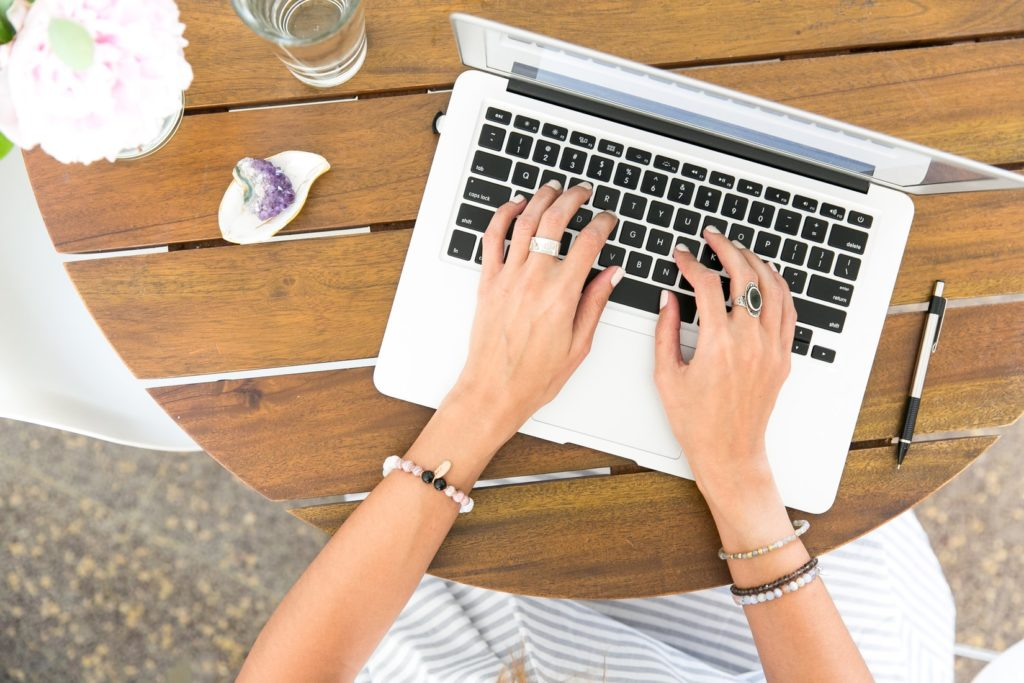 woman's hands typing on white macbook. searching for optimal keywords